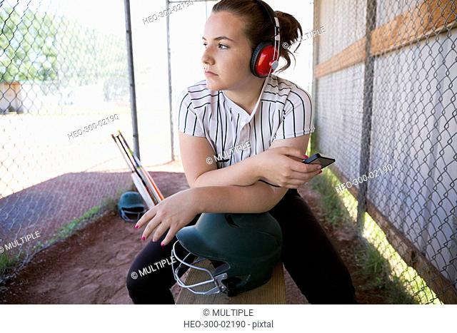 Serious middle school girl softball player listening to music with headphones in dugout