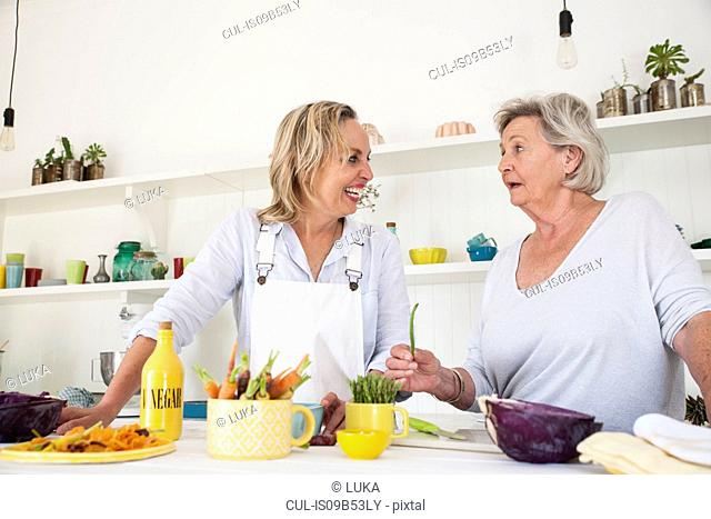 Senior woman and daughter chatting while preparing vegetables at kitchen table
