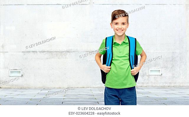childhood, school, education and people concept - happy smiling student boy with school bag over urban street background