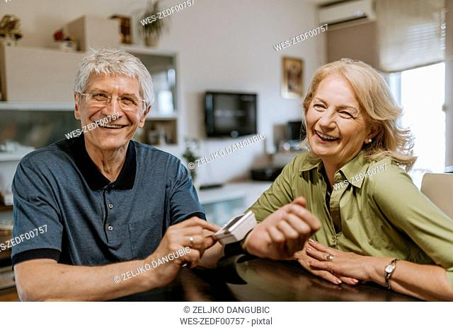 Smiling senior couple with blood pressure gauge