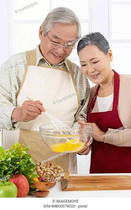 Senior couple standing in the kitchen and smiling happily