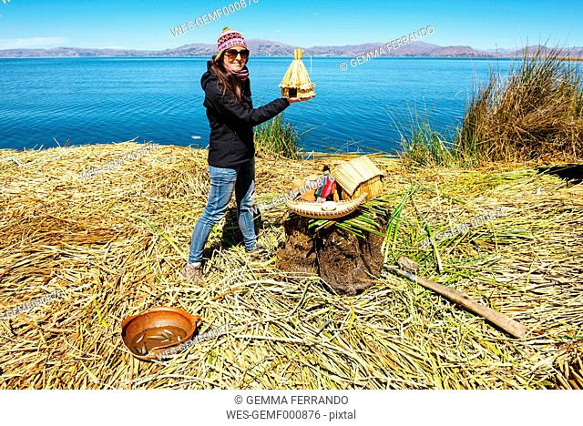 Peru, Titicaca lake, tourist on a floating island holding a miniature reproduction of the Uros reed houses