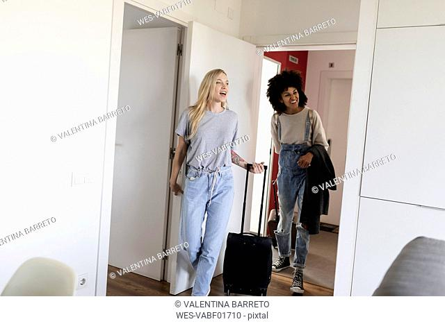 Two happy women with baggage arriving in accomodation