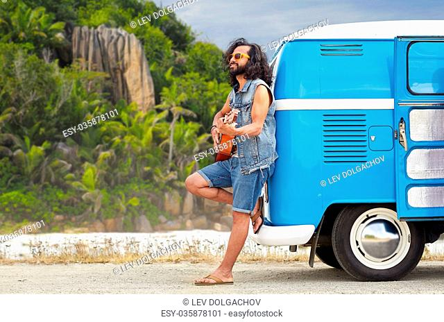 summer holidays, travel, music and people concept - young hippie man playing guitar and singing at minivan car over tropical island beach background