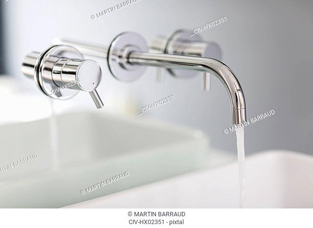Close up modern, minimalist bath faucet with running water