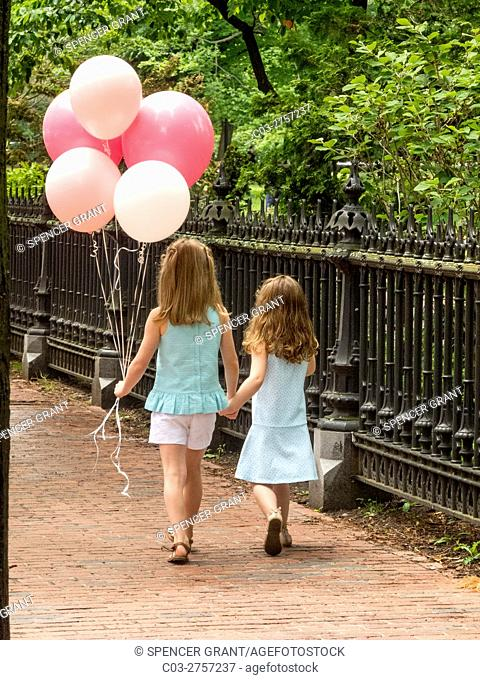 Two sisters hold hands as they walk past a park in Boston, MA. Note balloons and brick sidewalk