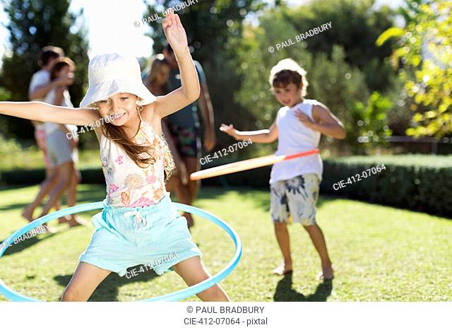 Children hula hooping in backyard