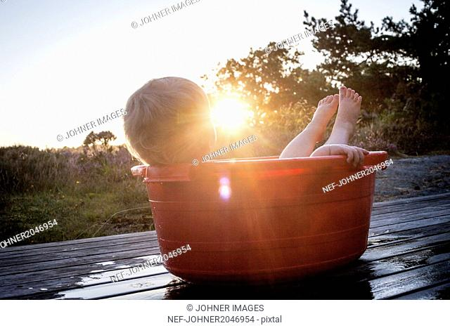 Small boy lying in baby bathtub at sunset