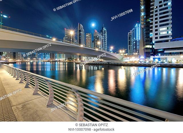 Dubai Marina with bridge, skyscrapers and full moon at night, New Dubai, UAE