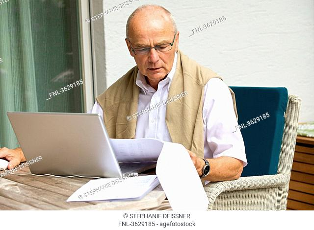 Senior man using laptop on terrace