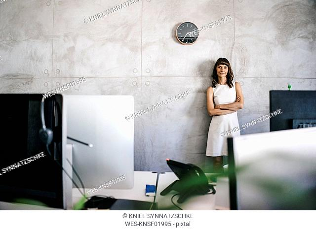 Businesswoman standing under wall clock with arms crossed