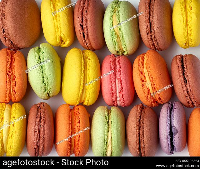 round baked multicolored macarons lie in a row, full frame, bright almond cake, close up