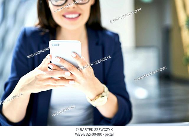 Close-up of smiling businesswoman using cell phone in office