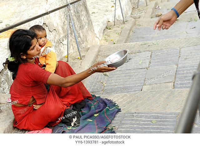 mother holding her baby whilst begging for money, the nepalis , life in kathmandu , kathmandu street life , nepal