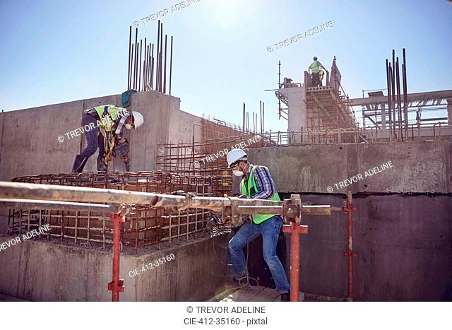 Construction workers working at sunny construction site