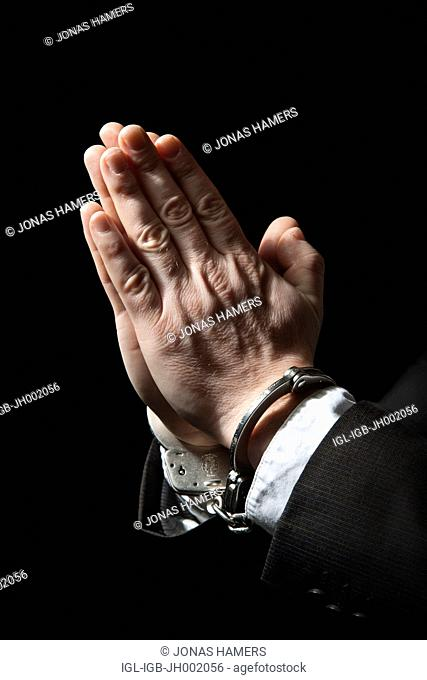 Picture shows man's hands praying with handcuffs