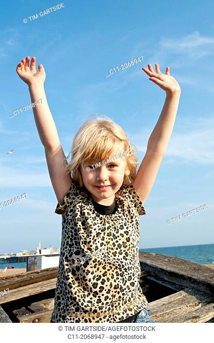 young girl smiling and waving;Brighton, East sussex, England, Europe, UK