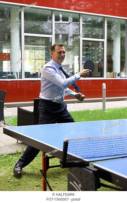 Businessman playing table tennis at creative office
