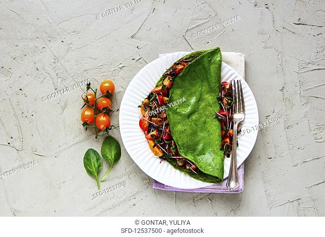 Green spinach omelette and fresh salad on white plate