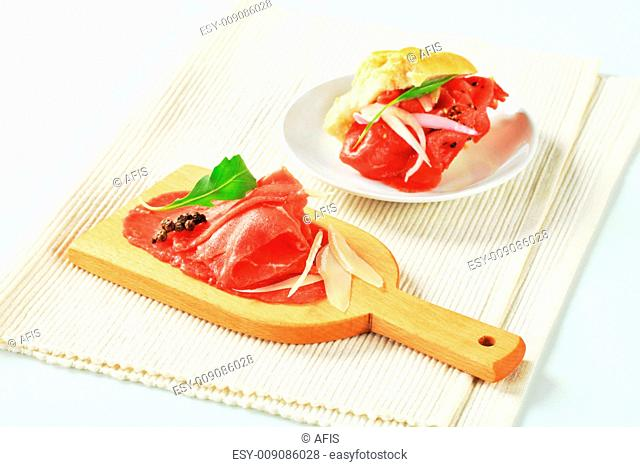 Thinly sliced raw beef meat on cutting board and Carpaccio sandwich