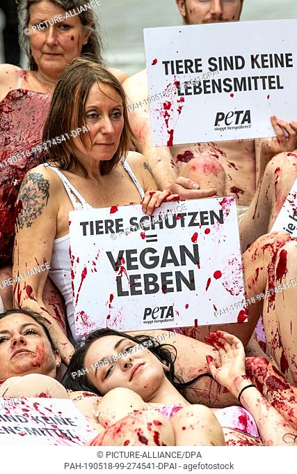 18 May 2019, Baden-Wuerttemberg, Stuttgart: Activists of the animal rights organization Peta lie on the ground covered with artificial blood and half-naked and...