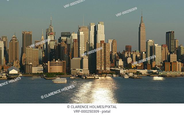 Sunlight reflects off the windows of the mid-town Manhattan skyline and the Hudson River during late afternoon