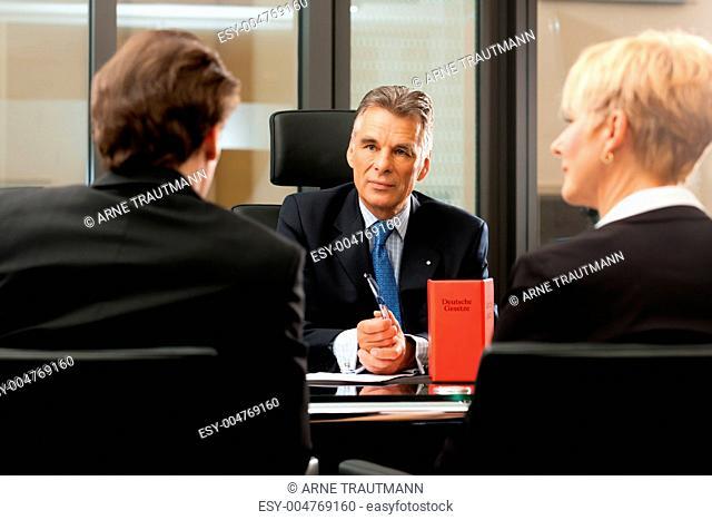 Anwalt oder Notar mit Mandanten in seinem Büro