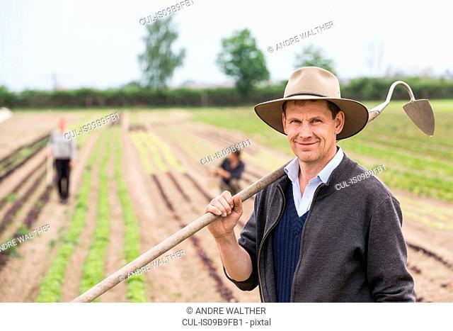 Portrait of farmer in field with hoe
