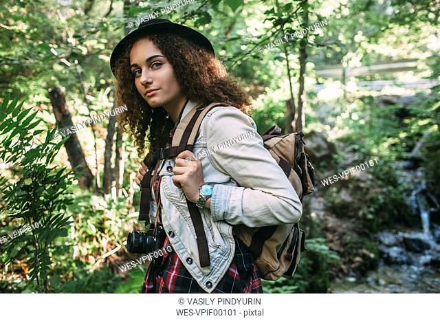 Portrait of teenage girl with backpack and camera in nature