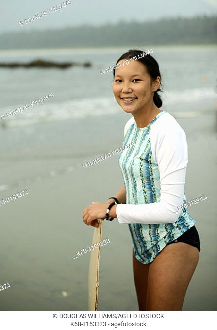 A teenage girl with her skim board on Flores Island, off the west coast of Vancouver Island, British Columbia, Canada