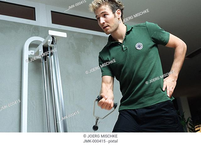 Young man at the fitness studio, gym, working out, doing exercises