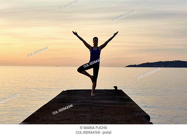 Young woman standing on pier, in yoga position, at sunset