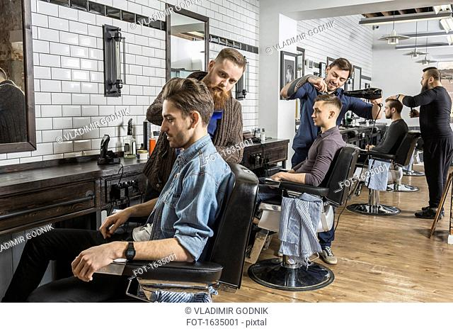 Hairdressers cutting male customer's hair in salon