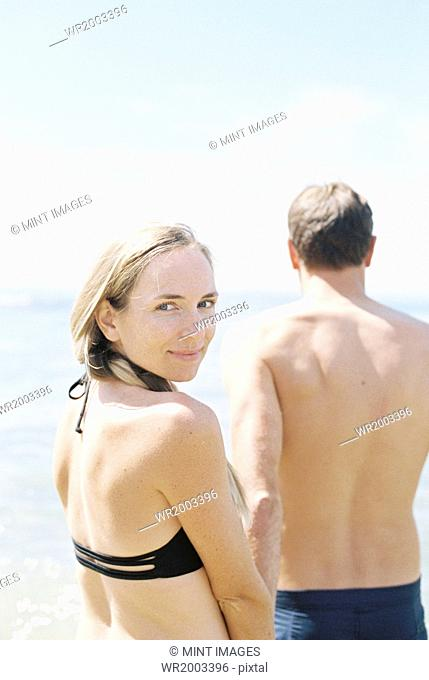 Couple in swimwear by the ocean, woman smiling at camera
