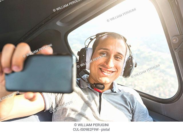 Man in passenger seat of aircraft, taking selfie with smartphone
