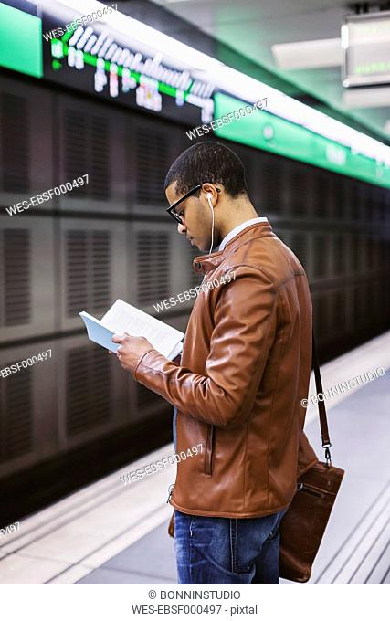 Spain, Barcelona, businessman standing at underground station platform reading book
