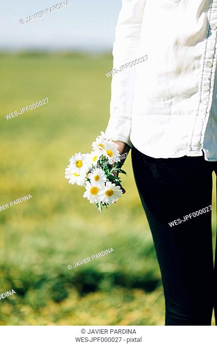 Cropped view of woman with flowers outdoors