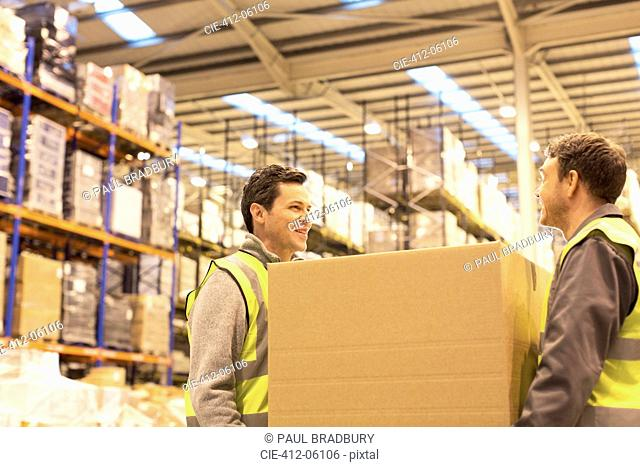 Workers carrying box in warehouse