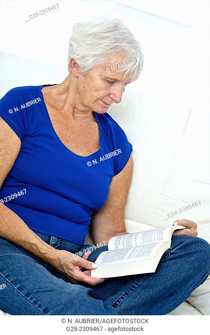 Senior woman sitting on her bed and reading a book