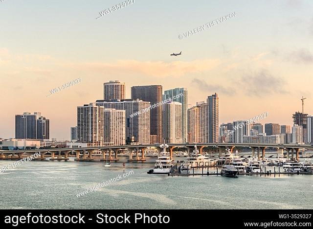 Miami, FL, United States - April 27, 2019: Miami City Skyline at dawn viewed from Dodge Island at Biscayne Bay. Long traffic bridge and luxury yacht in the...