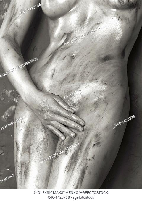 Closeup of a beautiful naked woman with shiny soiled body