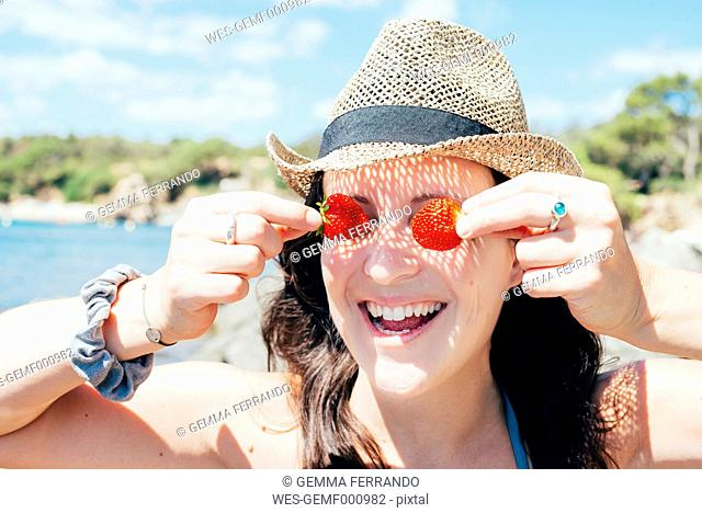 Portrait of smiling woman wearing straw hat on the beach covering her eyes with strawberries