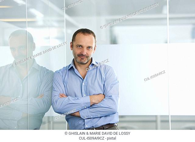 Businessman leaning against reflective wall