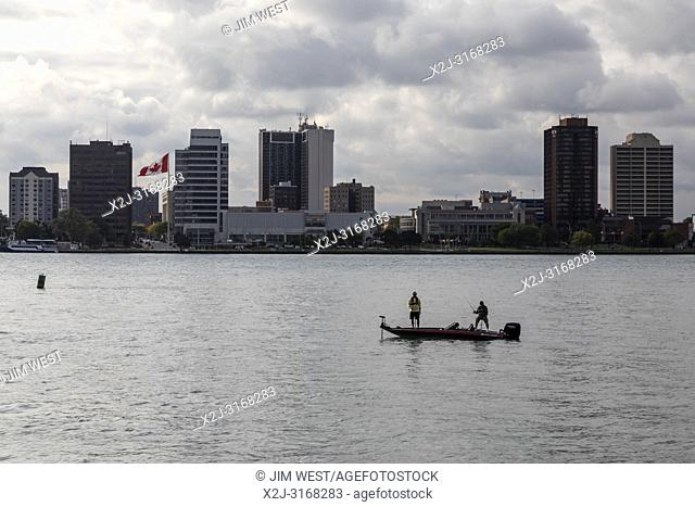 Detroit, Michigan - Two men fishing from a small boat on the Detroit River. Windsor, Ontario, Canada is on the far side