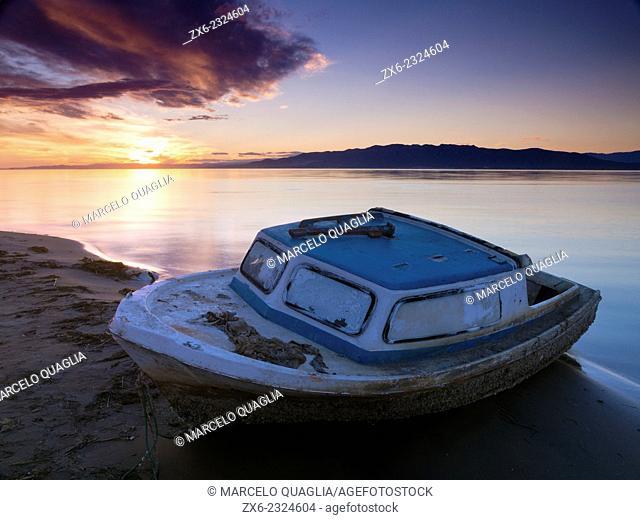 Stranded small fishing boat at Trabucador Isthmus. Alfacs Bay at sunset. Ebro River Delta Natural Park, Tarragona province, Catalonia, Spain