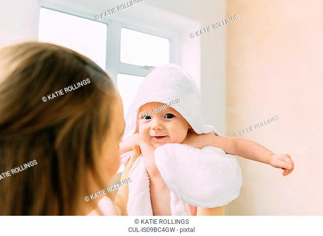Mother holding baby daughter wrapped in towel