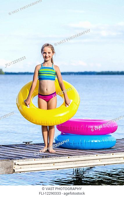 Girl on dock by Balsam Lake holding a yellow inflatable ring; Ontario, Canada