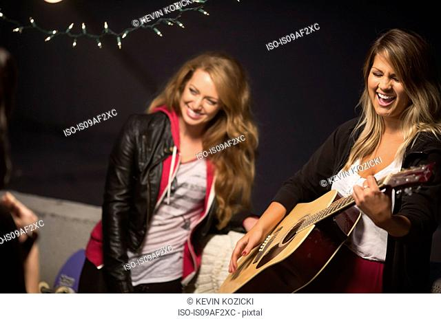 Female friends enjoying guitar music at rooftop party