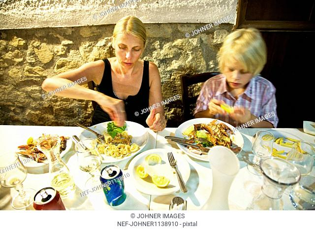 Mother and son eating in restaurant