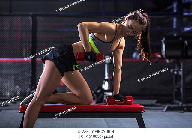 Young female athlete lifting weights in gym